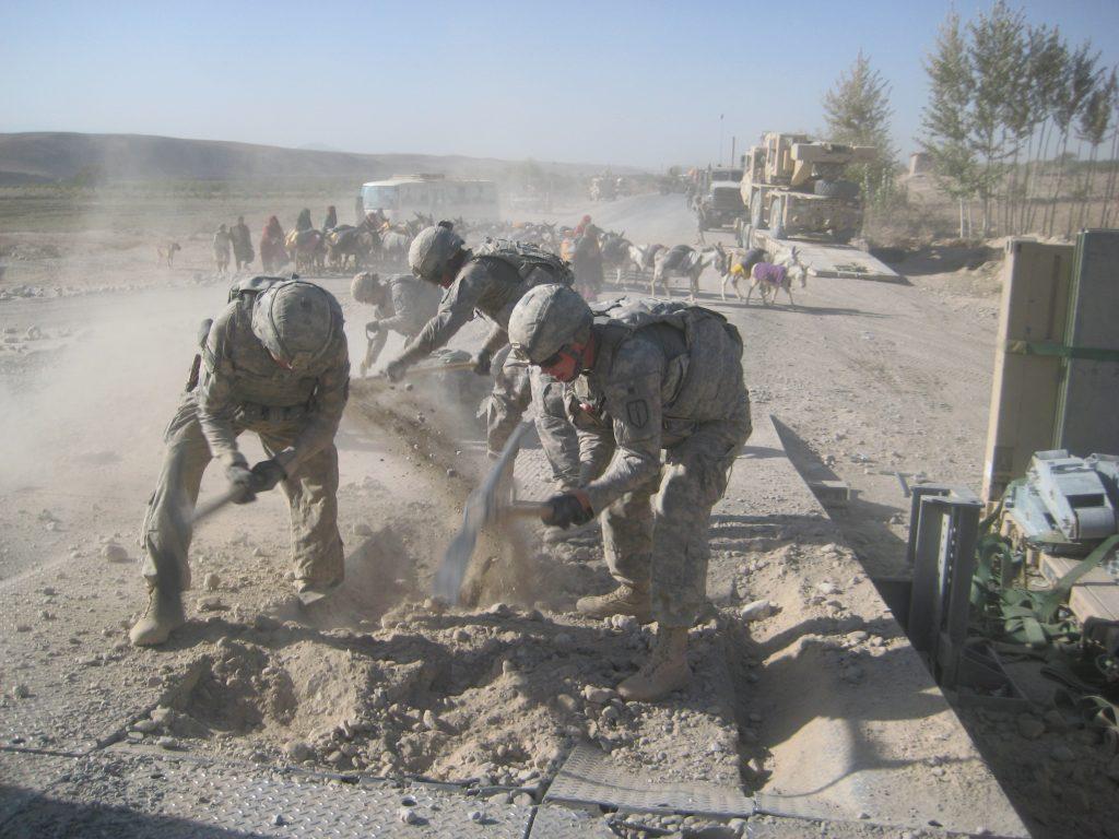 Local shepards move donkeys across Afghanistan Highway 1 as American service members repair a bridge.